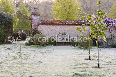 A Lutyens bench beside a frosty lawn on an April morning at Heale House, Middle Woodford, Wiltshire