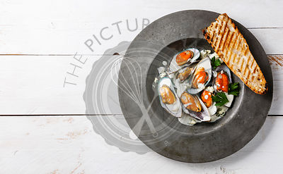 Shellfish Mussels Clams on plate with blue cheese sauce and bread copy space