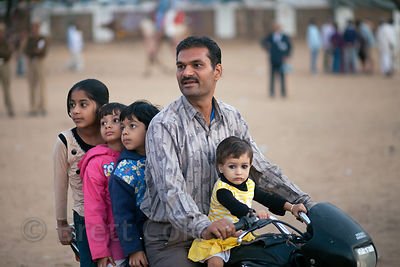 A man and his four children watch hot air balloons from their motorcycle, Pushkar, Rajasthan, India
