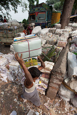 Paper recycling along the Hooghly River near Barabazar, Kolkata, India. The facility handles textbooks, newspapers, school papers, and office papers. They separate out high quality newspaper pages and inserts, which are sold to the thousands of food vendors in Kolkata to wrap street food in.