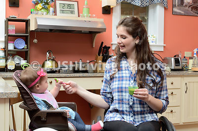 Young woman using a wheelchair feeding her baby