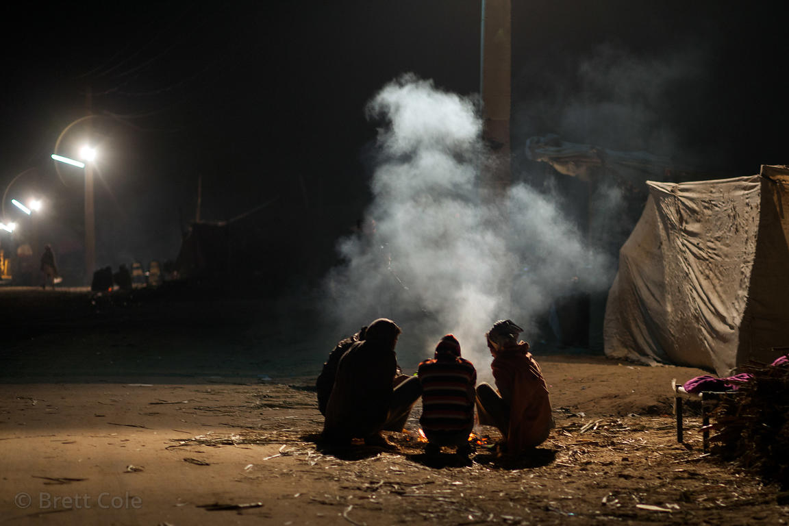 Men huddle next to a fire in the early morning at the Pushkar Camel Mela, Pushkar, India.