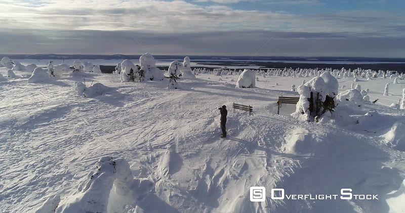 Hiking, Snowy Mountain, 4k Aerial View Around a Man Taking Pictures on the Top of a Fjeld Tunturi, Full of Snow Covered Trees...