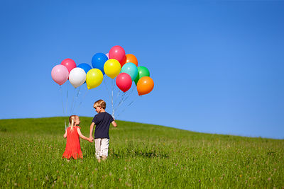 Children with colorful balloons in grass