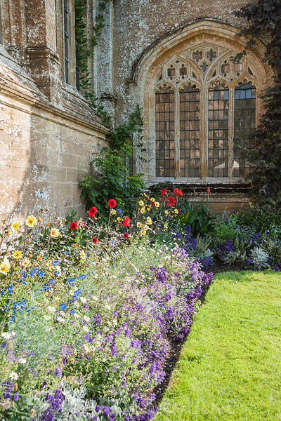 A border of bright annuals and herbaceous perennials in front of the historic house includes salvias, heliotropes, dahlias an...