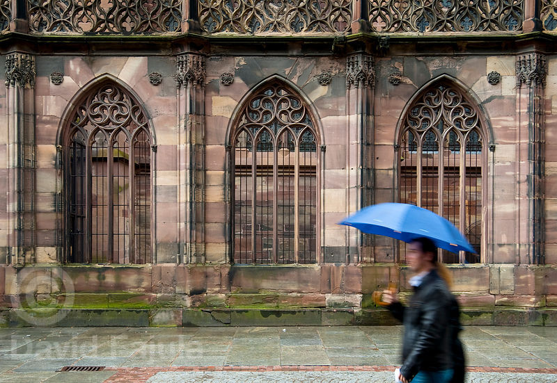 A couple walk in the rain in front of the Cathedral of Our Lady of Strasbourg (French: Cathédrale Notre-Dame-de-Strasbourg, G...