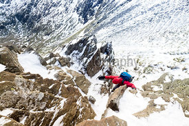 A walker climbing Striding Edge from Helvellyn in the Lake District.