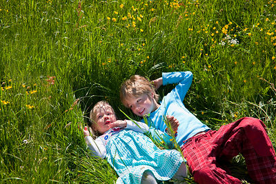 Children laying in field of flowers