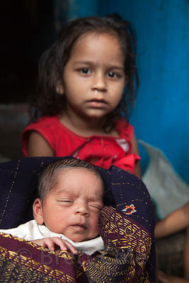 A girl and her baby sister in the Fakir Bagan area of Howrah, India
