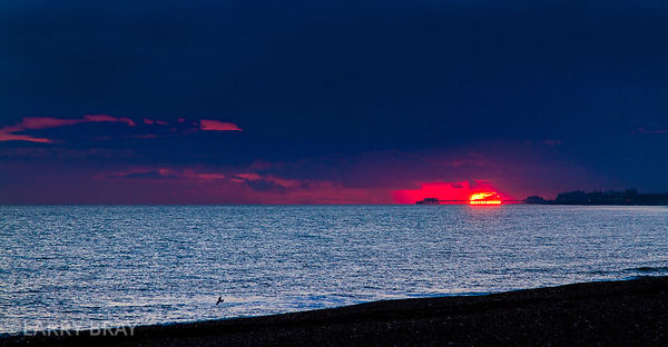 Panorama of sun sinking into sea behind Worthing Pier from Shoreham-by-Sea, West Sussex, UK