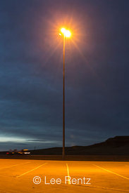Parking area and sodium-vapor lamp in a rest area along the eastbound lanes of I-90, South Dakota, USA