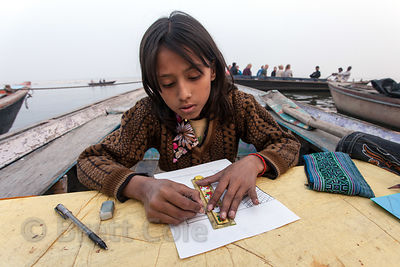 A girl does artwork in a fishing boat on the Ganges River, Varanasi, India.
