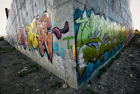 A graffiti-covered concrete wall near Dupont and Lansdowne is cutting through the dirt like a bow of a ship through the waves