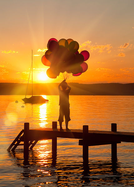 Boy holding balloons on wooden dock