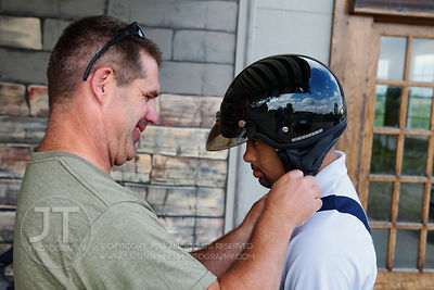 Scott Brownsberger helps Tyler Kurtz take off his helmet after they went for a ride on a Harley at the former Wallace Winery ...