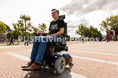 Couple using power wheelchairs on a promenade