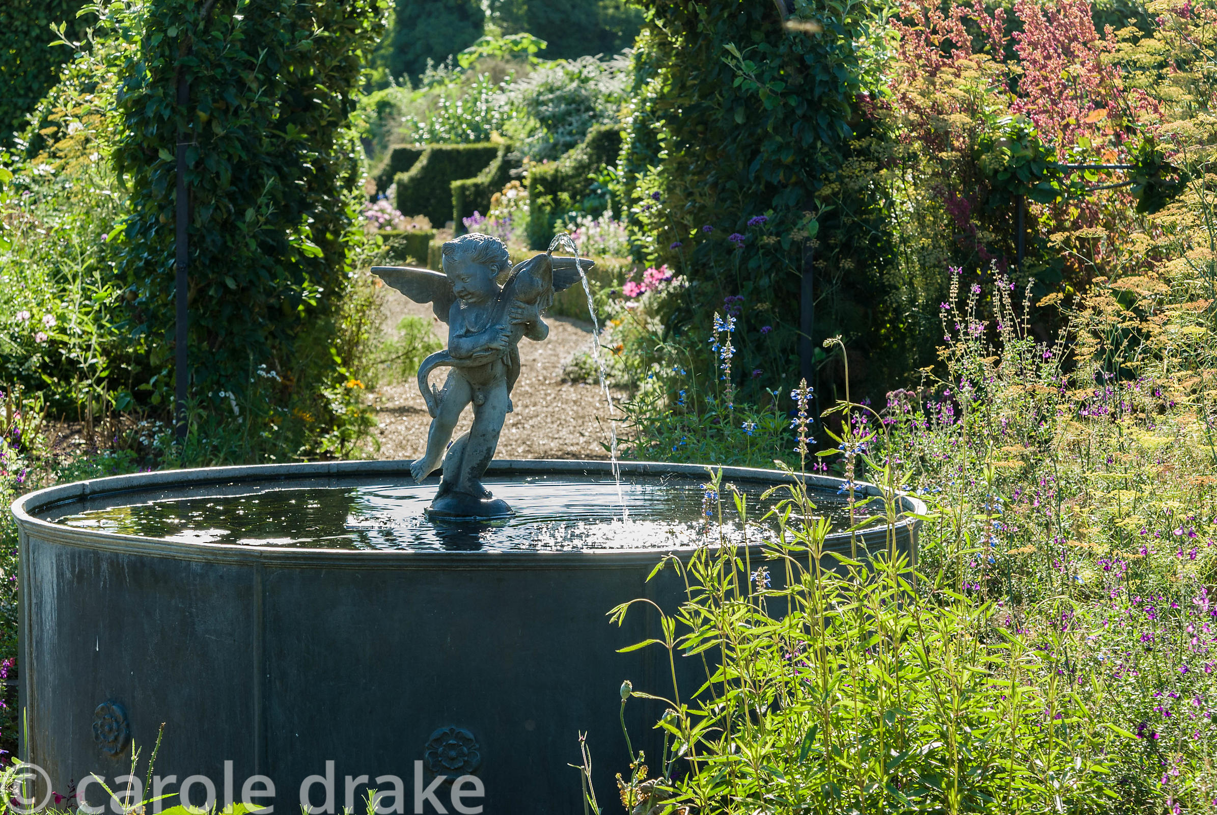 Lead fountain with putto and dolphin, surrounded by fennel and salvias, at the centre of the Organic Kitchen and Flower Garde...