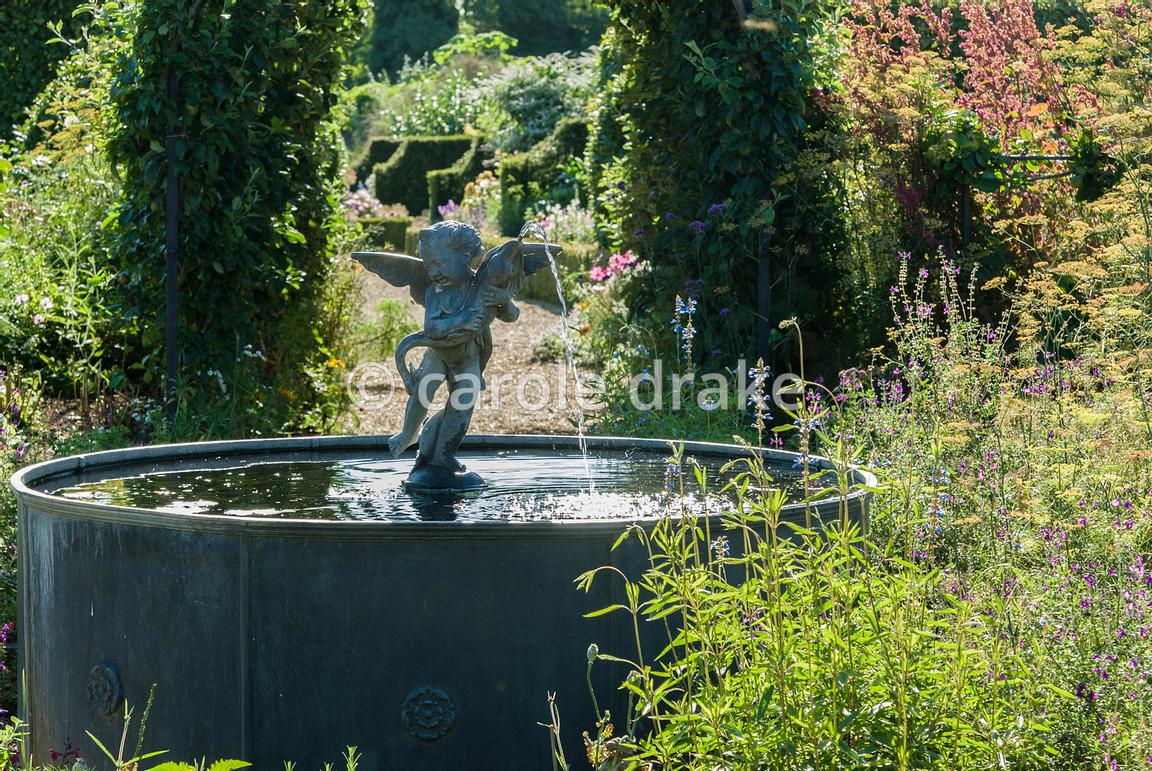 Lead fountain with putto and dolphin, surrounded by fennel and salvias, at the centre of the Organic Kitchen and Flower Garden, with apple tunnels shading the nearby paths. Arundel Castle Gardens, Arundel, West Sussex, UK