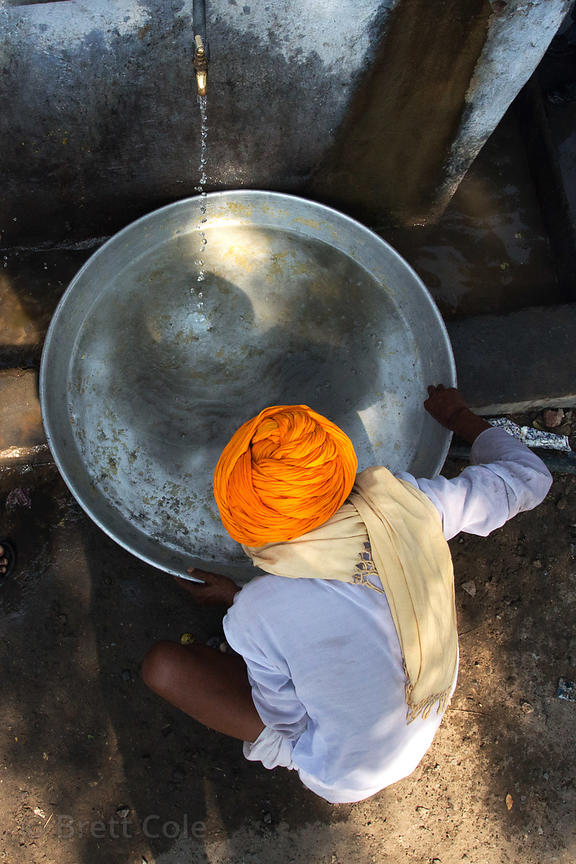A man washes a huge metal pan used to mix dough during a Hindu festival, Pushkar, Rajasthan, India
