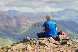LAKE DISTRICT, CUMBRIA, ENGLAND, UK - SEPTEMBER 02, 2017: A hiker sat down resting on the summit of Red Pike taking in the views over Buttermere in the English Lake District, UK.