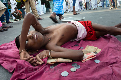 A Hindu boy with cerebral palsy begs during the Muslim Eid al-Adha festival, Red Road, Madian, Kolkata, India. I have the onl...