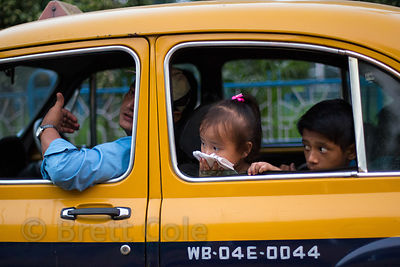 A girl shields her mouth from traffic fumes while riding in a taxi in Bhawanipur, Kolkata, India. Air pollution in Kolkata is...