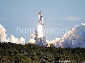 Through a cloud-washed blue sky above Launch Pad 39A, Space Shuttle Columbia hurtles toward space on mission STS-107.