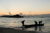Fishermen pusing a boat out to sea at sunrise, Sainte Luce Bay, Madagascar