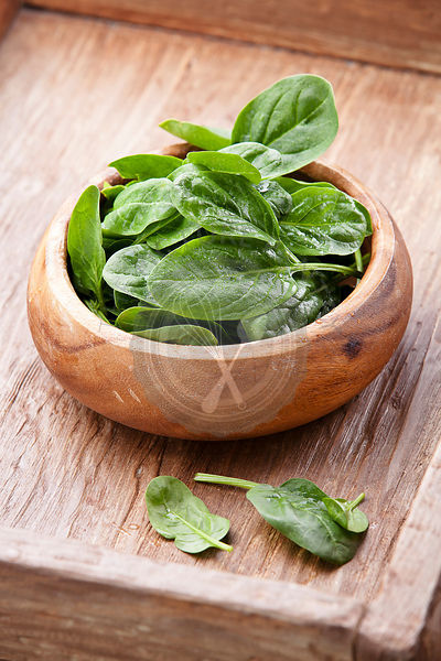 Young spinach in wooden bowl