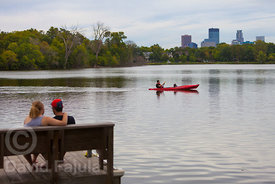 Couple by the Lake of the Isles with Minneapolis bulding on the background
