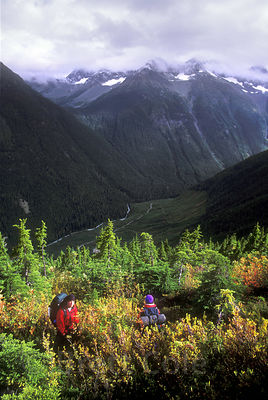 Hikers pause on a bushwhack up an unnamed trailless peak high in the Nusatsum Valley, Great Bear Rainforest of British Columb...