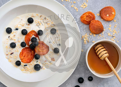 Breakfast oats with dried apricots, blueberries and milk beside a bowl of honey.