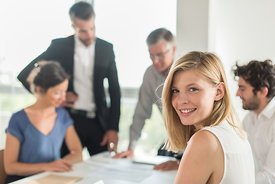 Portrait of a smiling blond assistant, she is turned back on her chair at an office business meeting. The team is sitting at ...