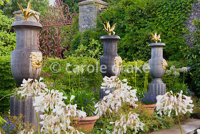 Carved oak urns with gilded lions' heads and topped with gilded agaves line the rill in the Collector Earl's Garden designed ...