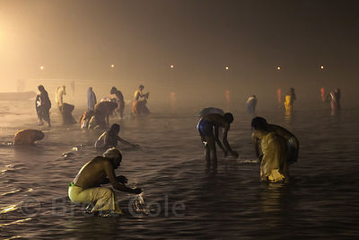 Hindu pilgrims bathe in the Bay of Bengal at night at the Gangasagar Mela, Sagar Island, India.
