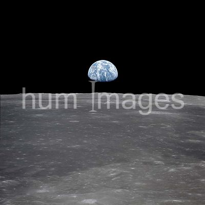 (July 1969) --- This view from the Apollo 11 spacecraft shows the Earth rising above the moon's horizon. The lunar terrain pi...