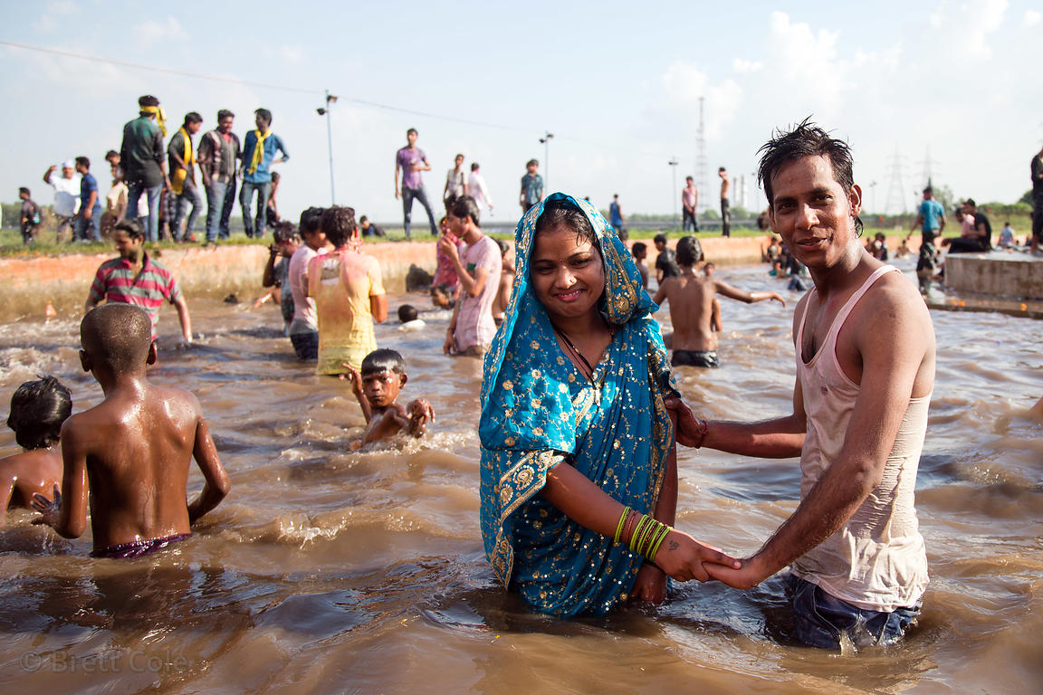 A couple hold hands while swimming along the Yamuna River during the Ganesh Chaturthi festival, Delhi, India
