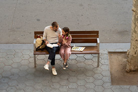 A father reading a book to his daughter on a bench at Passeig De Gràcia in Barcelona, Spain.