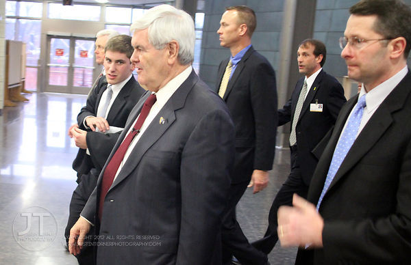 Republican Presidential candidate Newt Gingrich walks with his advisors and security staff in the Medical Education and Resea...