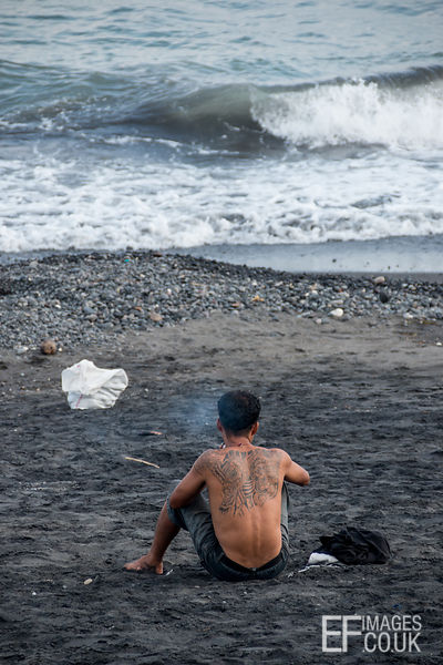 Man Smoking On A Black Sand Beach