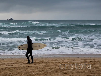 a surfer walks along the beach in Constantine Bay