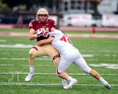 Coe College's Tyler Dralle (21) gets tackled by Central's Josh Scheible (48) during the second half of play at Clark Field in...