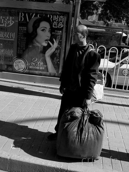 laden traveller at a Beijing bus stop