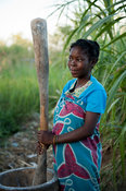 Woman pounding maize to make nsima, Chintheche, Malawi