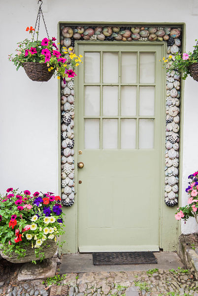Front door surrounded by decorative carved border, framed by hanging baskets and containers of annuals including petunias. Cl...