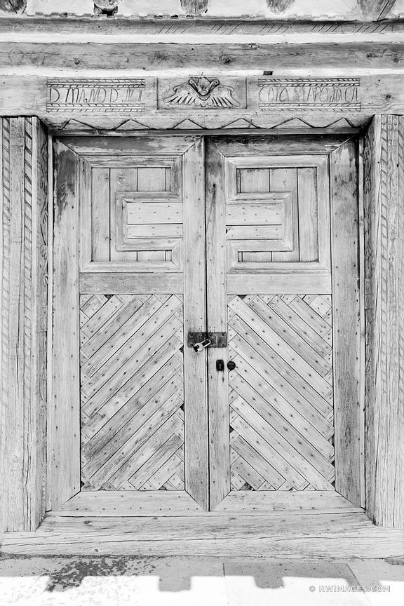 OLD DOOR SAN JOSE DE GRACIA CHURCH LAS TRAMPAS HIGH ROAD TO TAOS NEW MEXICO BLACK AND WHITE VERTICAL
