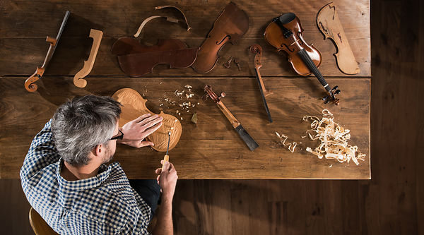 Top view. Artisan luthier working on the creation of a violin