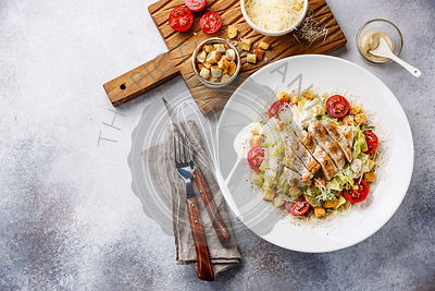 Caesar salad with chicken breast on gray background copy space