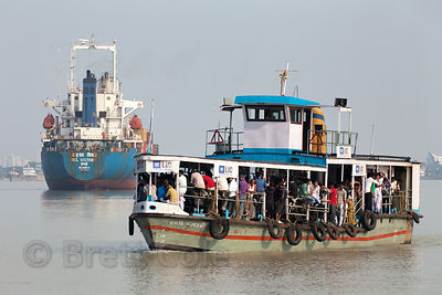 A ferry passes the ship Oel Victory (from Mumbai) on the Hooghly River near Metiabruz, Kolkata, India.