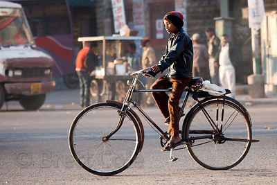 A boy rides a large bicycle down a main thoroughfare in Jodhpur, Rajasthan, India